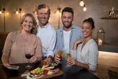 Portrait des amis heureux ayant les boissons et le repas Images stock