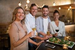 Portrait des amis heureux ayant les boissons et le repas Photographie stock