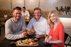 Portrait des amis heureux ayant les boissons et le repas Photo stock