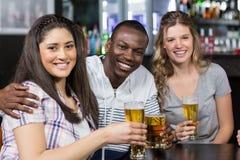 Portrait des amis heureux ayant une boisson Photos stock