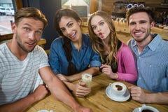 Portrait des amis heureux faisant des visages tout en ayant le café Photographie stock libre de droits