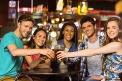 Portrait des amis heureux grillant avec la boisson et la bière Photo stock