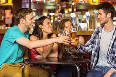 Portrait des amis heureux grillant avec la boisson et la bière Image libre de droits