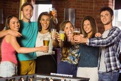 Portrait des amis heureux grillant avec le cocktail et la bière Photos stock