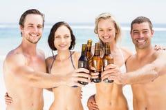 Portrait des amis heureux grillant des bouteilles à bière sur la plage Images libres de droits