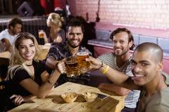 Portrait des amis heureux grillant des tasses de bière à la boîte de nuit Photos stock