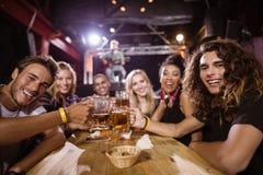 Portrait des amis heureux grillant des verres de bière tout en se reposant à la table Image stock