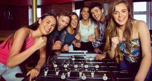 Portrait des amis heureux jouant le football de table Images libres de droits