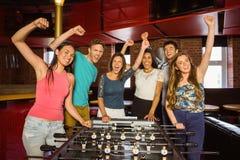 Portrait des amis heureux jouant le football de table Photographie stock