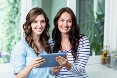 Portrait des amis heureux observant la vidéo sur le comprimé numérique Photo stock