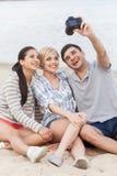 Portrait des amis heureux prenant la photo de lui-même sur la plage Image libre de droits