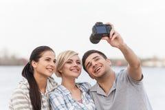 Portrait des amis heureux prenant la photo de lui-même sur la plage Photographie stock libre de droits
