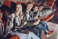 Portrait des amis heureux s'amusant sur le carrousel Photographie stock libre de droits