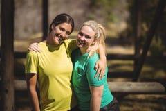 Portrait des amis heureux se tenant avec des bras autour pendant le parcours du combattant Photo libre de droits