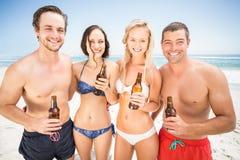 Portrait des amis heureux se tenant sur la plage avec des bouteilles à bière Photos libres de droits