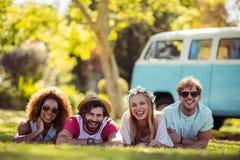 Portrait des amis heureux se trouvant sur l'herbe ensemble Photos libres de droits