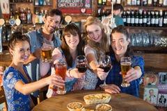 Portrait des amis heureux tenant des boissons dans la barre Photos libres de droits