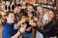 Portrait des amis heureux tenant des boissons tout en se tenant dans la barre Images libres de droits