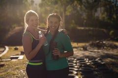 Portrait des amis heureux tenant la bouteille d'eau pendant le parcours du combattant Images stock