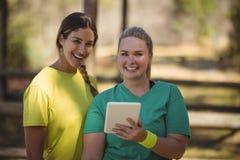 Portrait des amis heureux tenant le comprimé numérique pendant le parcours du combattant Images stock