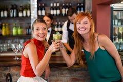 Portrait des amis heureux tenant un verre de genièvre devant le compteur de barre Photo stock