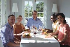 Portrait des amis heureux tout en ayant le repas Photo stock