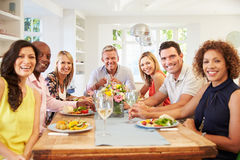 Portrait des amis mûrs autour du Tableau au dîner Images stock