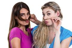 Portrait des amis malfaisants jouant avec des cheveux Photo stock