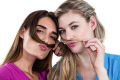 Portrait des amis malfaisants jouant avec des cheveux Photo libre de droits