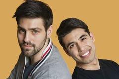 Portrait des amis masculins d'un jeune de nouveau au dos au-dessus du fond coloré Image libre de droits
