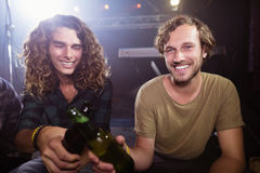 Portrait des amis masculins de sourire grillant des bouteilles à bière Photo stock