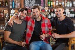 Portrait des amis masculins de sourire tenant des bouteilles à bière dans la barre Photos stock