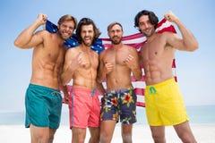 Portrait des amis masculins espiègles tenant le drapeau américain Photo stock