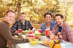 Portrait des amis masculins gais appréciant le repas extérieur ensemble Images stock