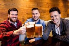 Portrait des amis masculins grillant la bière au restaurant Photo libre de droits