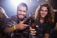 Portrait des amis masculins heureux grillant des bouteilles à bière Images stock
