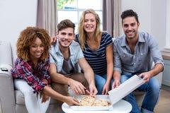Portrait des amis multi-ethniques appréciant la pizza à la maison Image libre de droits