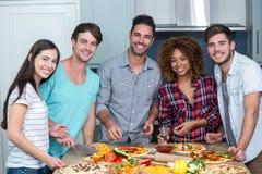 Portrait des amis multi-ethniques heureux préparant la pizza à la maison Image libre de droits