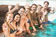 Portrait des amis ondulant des mains dans la piscine Photos stock