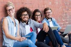 Portrait des amis s'asseyant contre le mur Photo libre de droits