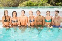 Portrait des amis s'asseyant dans la piscine Photographie stock libre de droits