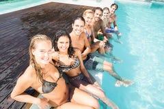 Portrait des amis s'asseyant dans la piscine Photos libres de droits