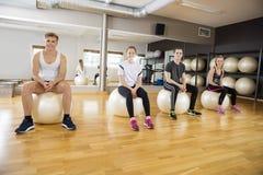Portrait des amis s'asseyant sur la boule d'exercice au gymnase Photo libre de droits