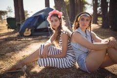 Portrait des amis s'asseyant sur le champ contre la tente Photos stock