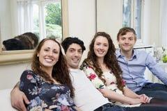 Portrait des amis s'asseyant sur le sofa Image libre de droits