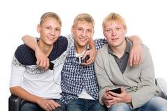 Portrait des amis s'asseyant sur un divan Image stock