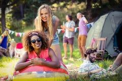Portrait des amis se penchant sur le ballon de plage au terrain de camping Images libres de droits