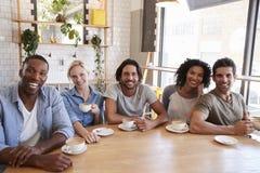 Portrait des amis se réunissant autour du Tableau dans le café Photo stock