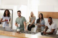 Portrait des amis se réunissant pour le café dans la cuisine moderne Photographie stock