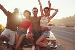Portrait des amis se tenant à côté de la voiture classique Image libre de droits